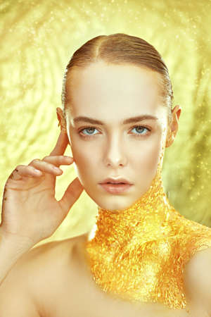 Beauty, fashion gold concept. Portrait of a beautiful girl model with golden skin and golden make-up on a sparkling background with golden lights. Jewelry. Cosmetics and beauty care. Banque d'images