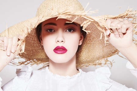 Close up portrait of a beautiful romantic girl in a white blouse and straw hat. Summer season. Beauty and cosmetics.
