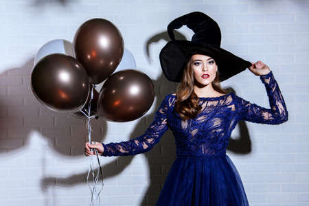 A beautiful lady in a costume of witch. Halloween. Masquerade. Celebration.
