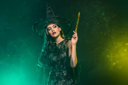 A portrait of a beautiful witch in a hat holding a magic stick. Halloween. Celebration. Stok Fotoğraf
