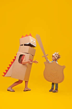 Portrait of a cute boy in costume of knight with cardboard armor is fighting the cardboard dragon. Childhood dreams. Full length portrait on a yellow background.