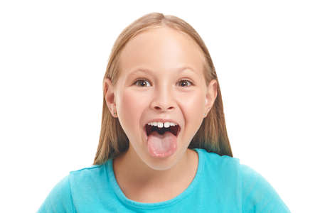 Emotional eight year old girl is teasing someone with his tongue out. Studio portrait on a white background. Copy space Stockfoto