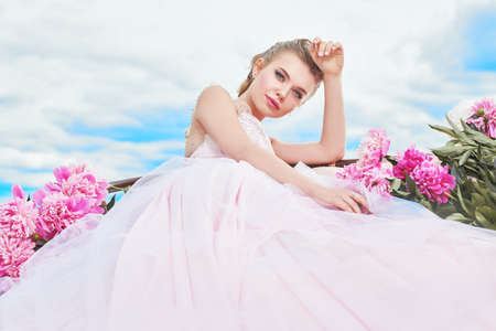 Fashion shot. Gorgeous young woman in a luxuriant pale pink dress lies on the couch among beautiful peony flowers. The backdrop of a landscape with blue sky and white clouds. Wedding style.