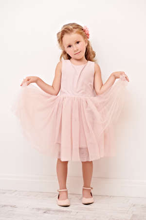 Full length portrait of a cute little girl in a beautiful light dress standing in a white room. Studio shot. Happy childhood. Kids fashion.