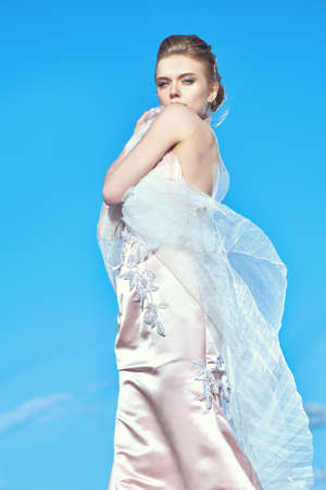 Beauty, fashion concept. Portrait of a beautiful young woman bride in elegant evening dress against the blue sky.
