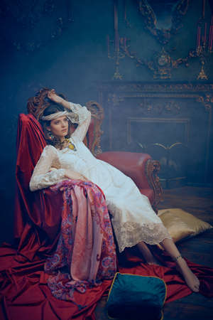 Bohemian lifestyle. Beautiful young woman in elegant lace dress and jewelry posing in a vintage armchair in a luxurious interior. Fashion shot, oriental style. Stockfoto