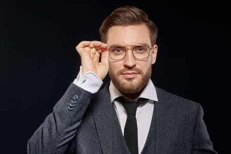 Portrait of a handsome serious businessman wearing suit and glasses on a black background. Men's beauty, fashion. Optics for men.