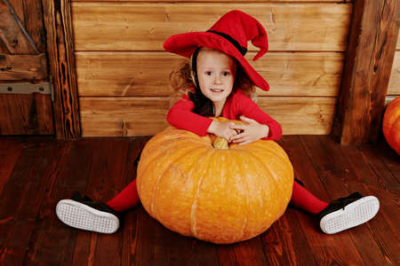 Funny little girl in a witch costume sits behind a big pumpkin over wooden background. Halloween. Imagens