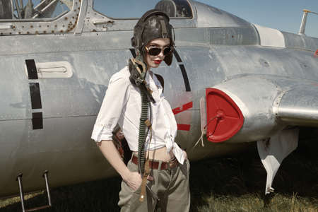 Portrait of a beautiful girl pilot wearing helmet and sunglasses stands next to her fighter jet at the airfield. Military aircraft.