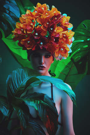 Fashionable female model posing among tropical plants in a beautiful orchid headgear. Beauty and fashion concept. Tropical vacation. Stock fotó