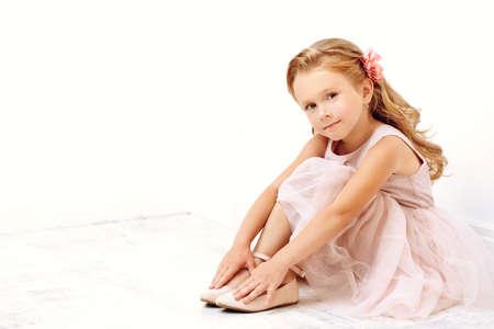 Portrait of a cute little girl in a beautiful light dress sitting on the floor in a white room. Studio shot. Happy childhood. Kids fashion. Foto de archivo