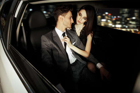 Glamorous passionate couple in a car. Beauty, fashion.