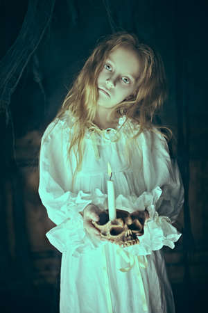 Halloween. A ghost girl in a nightgown wanders through the old house at night. Stock fotó