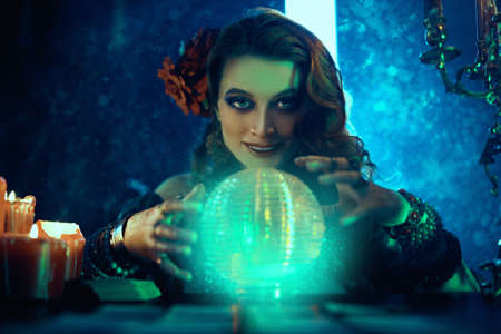 Bewitching fortune teller woman reading future on magical crystal ball.