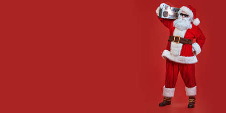 Cool DJ Santa Claus in sunglasses holds tape recorder on a festive red background. Christmas songs and music. New Year party. Stock Photo
