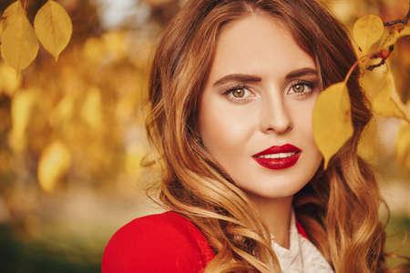 Beauty portrait. Beautiful young woman over sunny autumn background. Archivio Fotografico