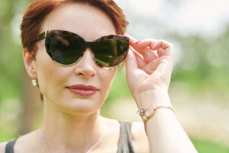 Happy middle-aged woman in modern sunglasses in summer park. Close up portrait.