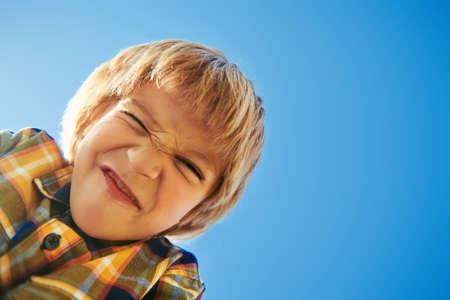 Cute little boy smiling against the blue sky. Retro style. Children's fashion. Autumn and summer season.