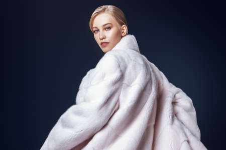 A portrait of a young fashionable woman in a white mink coat. Beauty, fashion.