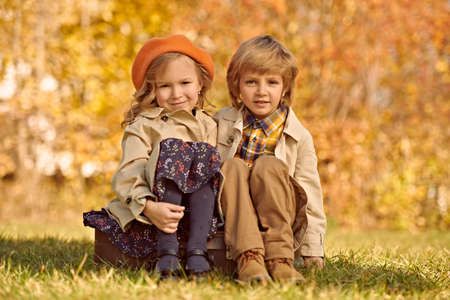 Happy romantic kids boy and girl sit on old fashioned suitcase in autumn park. Children's fashion. Retro style.