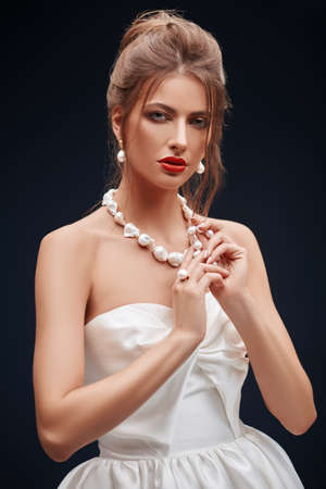 Portrait of a beautiful young bride woman in a fashionable white dress on a black background. Wedding fashion. Make-up and hairstyle.