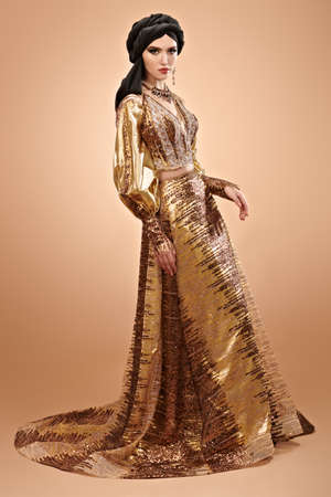 Oriental beauty woman. Full length portrait of a beautiful arabian woman in traditional dress, with traditional oriental make-up and black hijab. Banque d'images