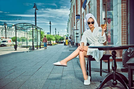 Glamorous young woman in a white terry dressing gown with a white towel on her head sits at a table in a street cafe with a glass of wine.