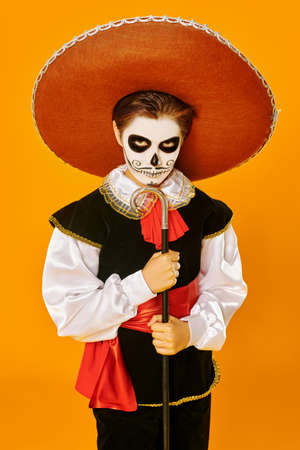 Portrait of a handsome boy with sugar skull makeup over bright yellow background. Halloween. Dia de los muertos. Day of the dead. Copy space. Standard-Bild