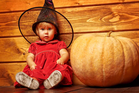 A little girl in a smart red dress in a witch's hat is sitting next to pumpkin. Children's Halloween party. Fashion for kids.