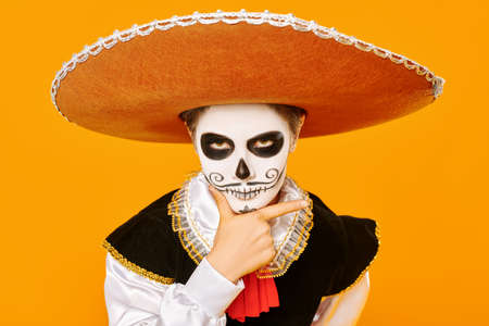Portrait of a handsome boy with sugar skull makeup over bright yellow background. Halloween. Dia de los muertos. Day of the dead.