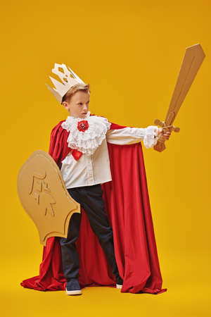 Full length portrait of a cute brave boy in a knight costume with cardboard armor. Yellow background. Childhood dreams and fantasy. Carnival, Theater. Standard-Bild