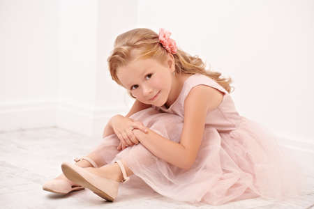 Portrait of a cute little girl in a beautiful light dress sitting on the floor in a white room. Studio shot. Happy childhood. Kids fashion.