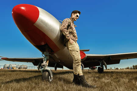 Handsome man pilot wearing military uniform stands by his fighter jet at the airfield. Military aircraft. Full length portrait.