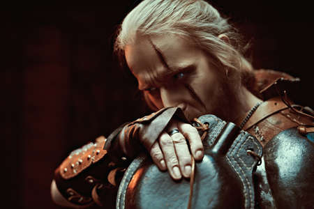 A medieval warrior in armor drinks from a flask by candlelight. Stage portrait. The Witcher man. Stock Photo
