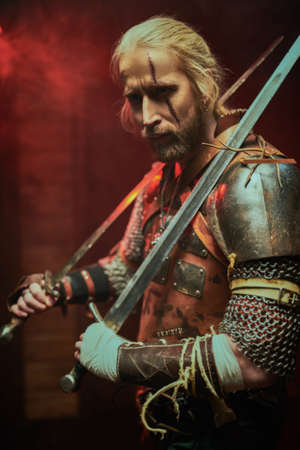 Portrait of a brave medieval warrior in armor with swords on a dark background. The Witcher man.