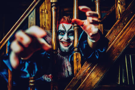 A close up portrait of a smiling clown pulling hands from behind stairs railings. Halloween, carnival.