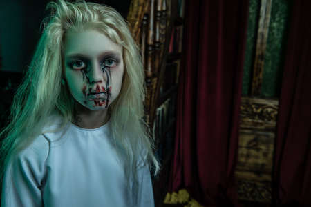 A portrait of a scary pale girl from a horror film in a room. Zombie, halloween.