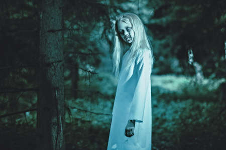 A portrait of a scary pale girl from a horror film in the forest. Zombie, halloween.