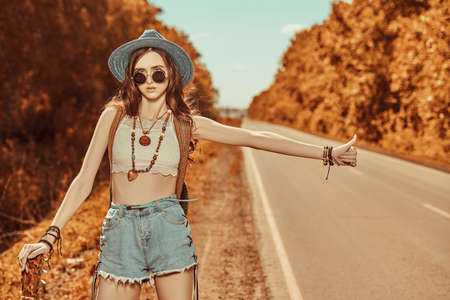 Pretty hippie girl with a guitar and a backpack hitchhiking on a highway. Spirit of freedom. Summer vacation adventure.