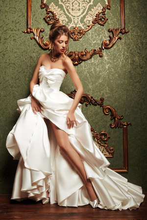 Magnificent young woman in luxurious white dress and precious jewelry posing in a luxury apartment. Classic vintage interior. Wedding fashion.