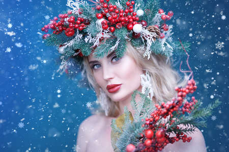 Beautiful happy young woman with a Christmas spruce wreath on her head, decorated with Christmas balls, berries and snowflakes. Blue snowy background. Copy space.