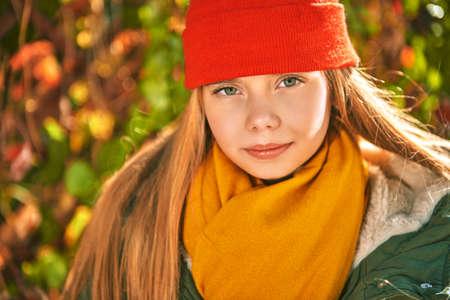 Autumn season. Close up portrait of a beautiful girl teenager on a sunny autumn day.