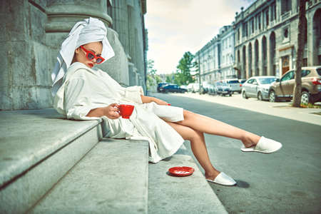 Glamorous lifestyle. Stunning woman in a white terry dressing gown with a white towel on her head and elegant sunglasses alluring on a city street with a cup of tea. Fashion shot. Imagens
