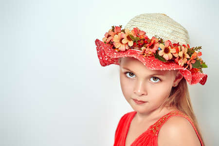 Pretty eight year old girl in hat is smiling. Studio portrait on a white background. Copy space.