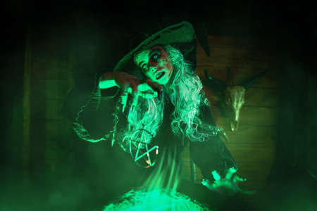 Horrible old witch brews witchcraft in her cauldron surrounded by magical green light. Halloween. Scary tales. Stock Photo