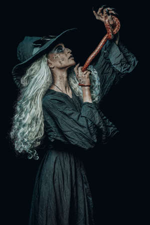 Halloween. Portrait of a scary ugly witch talking with her poisonous snake on a black background. Scary tales. Witchcraft.