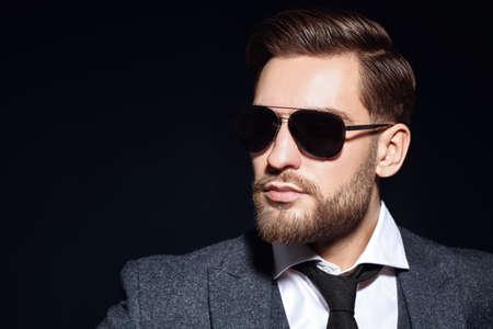 Portrait of a handsome businessman wearing suit and sunglasses on a black background. Men's beauty, fashion. Optics for men. Copy space.