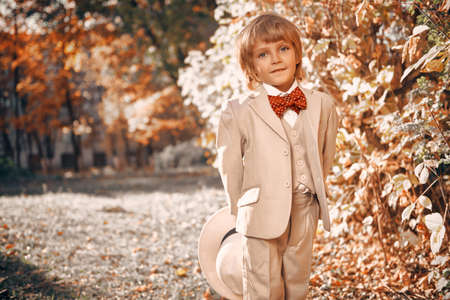 Portrait of a cute funny little boy in elegant white suit and white hat walking through a beautiful autumn park. Retro style. Children's fashion.