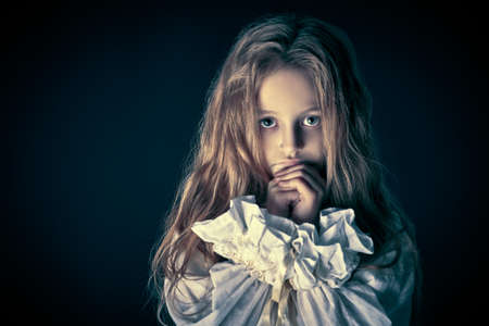 Scary little girl ghost in a white nightgown folded her hands in prayer. Black background. Halloween. Stock fotó