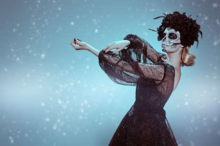 Dia de los muertos. Full length portrait of a beautiful Calavera Catrina. Fashion model with sugar skull makeup. Day of The Dead. Halloween. Stock Photo